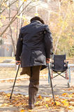 Handicapped one-legged man walking on crutches. View from behind of handicapped one-legged man walking on crutches in autumn park he heads for his wheelchair Royalty Free Stock Image