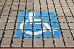 Handicapped parking spot - transportation infrastructure road markings and sign. Royalty Free Stock Images