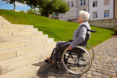 Handicapped person looking at. Elderly woman in wheelchair looking at stairs Royalty Free Stock Photography