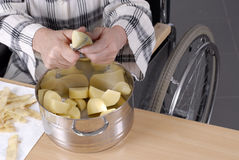 Handicapped person peeling potatoes Royalty Free Stock Image