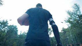 Handicapped person with robotic prosthesis stands on a basketball court, holding a ball. 4K