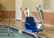 Handicapped pool lift. Chair over an indoor pool Stock Photos