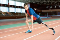 Handicapped Runner Stretching in Stadium stock photography