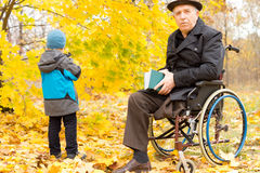 Handicapped senior man and child. Handicapped senior men with one leg amputated accompanying a young child on a day out in a colourful yellow autumn park sitting Royalty Free Stock Photos