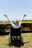 Handicapped senior woman. Rear view of handicapped senior woman with open arms in home garden Stock Images
