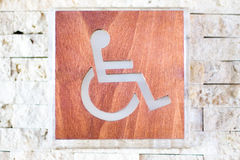 A handicapped sign. Shallow DOF. A handicapped sign of wood and glass on a stone wall. Shallow DOF Stock Images