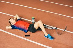 Handicapped Sportsman Resting on Running Track Royalty Free Stock Photography