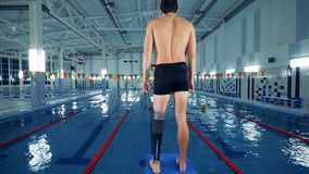 Handicapped swimmer warms up near a pool, leg prosthesis. 4K stock video
