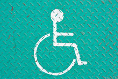 Handicapped symbol. White handicapped symbol on green plate Stock Image