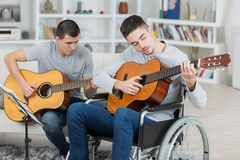 Handicapped teenager and friend playing guitar. Handicapped teenager and friend playing the guitar Royalty Free Stock Photography