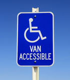 Handicapped van parking sign. In blue and white on blue sky background stock photo