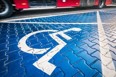 Handicapped wheel chair sign, designated parking place, blurred stock photography