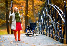 Handicapped woman raising her crutches Stock Images