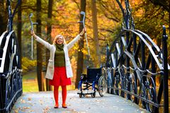 Handicapped woman raising her crutches Stock Photos