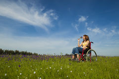 Handicapped woman on wheelchair. Happy handicapped woman on a wheelchair over a green meadow Stock Photography