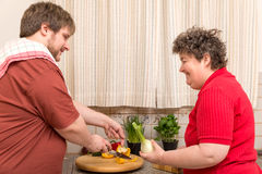 Handicapped woman and a young man in the kitchen Royalty Free Stock Image