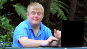 Handicapped young man typing on laptop in garden.