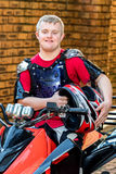Handicapped young quad bike rider holding helmet. Stock Photo