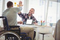 Handicappi dare dell'uomo d'affari alto--cinque al collega in ufficio fotografia stock libera da diritti