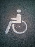 Handicappi il simbolo su asfalto in un parcheggio fotografia stock