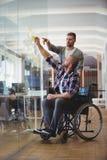 Handicappi l'uomo d'affari con il collega che attacca le note adesive in ufficio fotografia stock