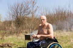 Handicappi l'uomo senior sulla sua sedia a rotelle al parco fotografia stock