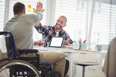 Handicapzakenman die hoog-vijf geven aan collega in bureau royalty-vrije stock foto
