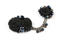 Handicraft brooch and pendant in the form of black flowers from fabric, connected by a chain as a female adornment.  Stock Photos