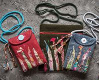 Handicraft, embroidery, handmade bags on a gray old background stock photos