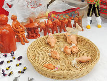 Handicraft folk knick-knacks. Russian folk handicraft figuline penny whistles, figurines, beaded brooches and basket dish on the tablecloth Stock Images