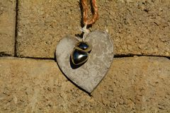 Handicraft heart. With two silvered small hearts against a brick wall Royalty Free Stock Images