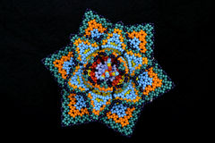 Handicrafts huichol art. Colorful mexican craftwork  created by huichol people in Jalisco, Mexico.Tiny beads are handwoven to create their sacred flower Royalty Free Stock Photo