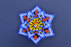 Handicrafts huichol flowers. Colorful mexican craftwork  created by huichol people in Jalisco, Mexico.Tiny beads are handwoven to create their sacred flower Royalty Free Stock Image