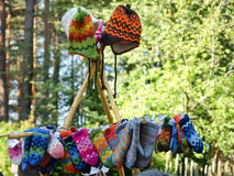 Handicrafts. Knitted mittens and hats exibited on wooden stand Royalty Free Stock Images