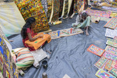 Handicrafts are perpared for sale by rural Indian man and woman in Pingla village, India Stock Image