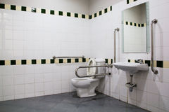 Handikapp badrummet med hastigt greppstänger och den keramiska tegelplattan Arkivfoton