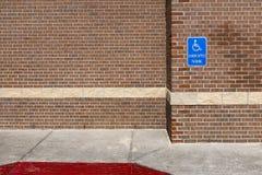 Handikapp blått parkera tecknet på en vägg för röd tegelsten av en kontorsbyggnad i det enigt mättar av Amerika royaltyfria foton