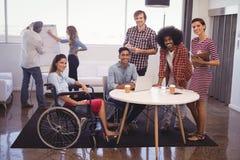 Handikapp den kvinnliga ledaren med kollegor i idérikt kontor royaltyfria foton
