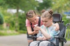 Handikapp ett rörelsehindrat barn i en avslappnande yttersida för rullstol med hennes syster royaltyfria foton