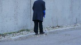 Handikappad folkbakgrund för åldring gamala mannen går offentligt med kryckor arkivfilmer