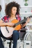 Handikappad gitarrist för flicka som sitter på rullstolen royaltyfri fotografi