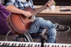 Handikappad hängiven musiker som spelar gitarren Royaltyfri Foto