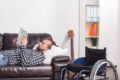 Handikappad man för barn som ligger på en soffa Arkivbilder