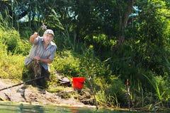 Handikappad man som gjuter hans linje, när fiska Arkivfoto