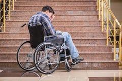 Handikappade personermannen på rullstolen som har problem med trappa royaltyfria bilder