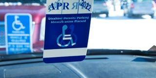 Handikappat parkera tecken och handikappade plakat i bilfönster arkivfoton