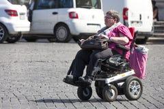 Handikappkvinna med den lilla bilen (rullstolen) Arkivfoton