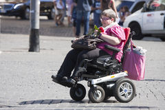 Handikappkvinna med den lilla bilen (rullstolen) Arkivbilder
