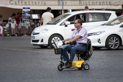 Handikappman med den lilla bilen Arkivbilder