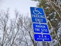 Handikappparkering undertecknar parkerar in mot träd Royaltyfria Bilder
